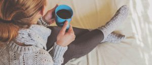 woman-in-sweater-with-warm-drink